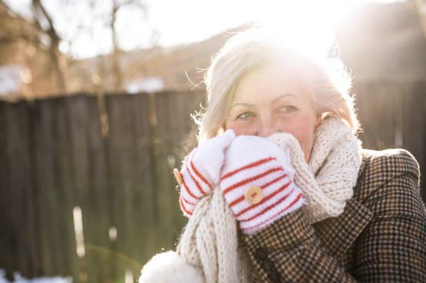beautiful senior woman on a walk against wooden fence. - kalte sonne stock-fotos und bilder