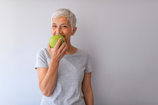 Portrait of happy mature woman holding granny smith apple at home. Beautiful senior woman over grunge grey wall eating green apple with happy face smiling.