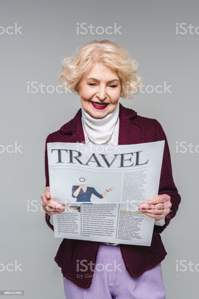 beautiful senior woman reading travel newspaper isolated on grey zbiór zdjęć royalty-free