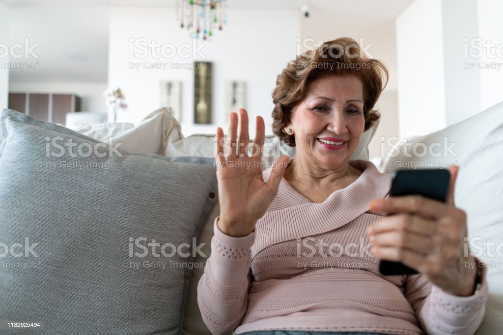 Beautiful senior woman relaxing on couch on a video call greeting looking very happy - Royalty-free A usar um telefone Foto de stock