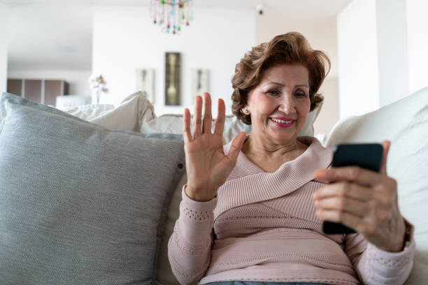 beautiful senior woman relaxing on couch on a video call greeting looking very happy - video call imagens e fotografias de stock