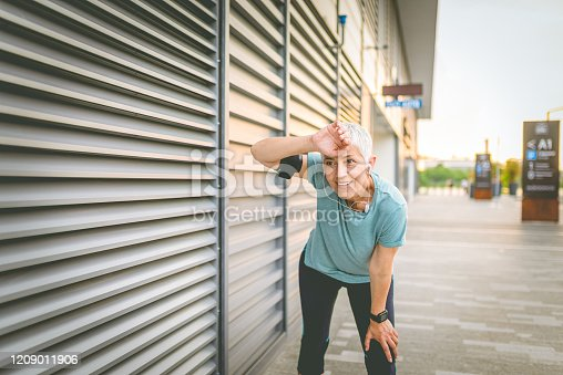 1057638814 istock photo Beautiful senior woman resting after work out outdoor. 1209011906