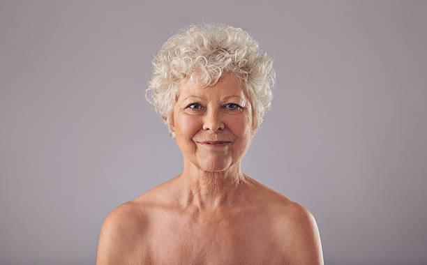 hermosa mujer mayor sin camisa contra fondo gris - desnudos fotografías e imágenes de stock