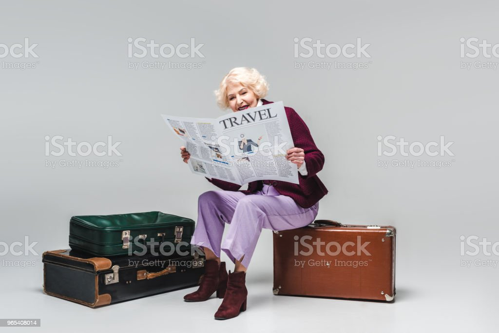 beautiful senior woman sitting on vintage suitcase and reading travel newspaper on grey royalty-free stock photo