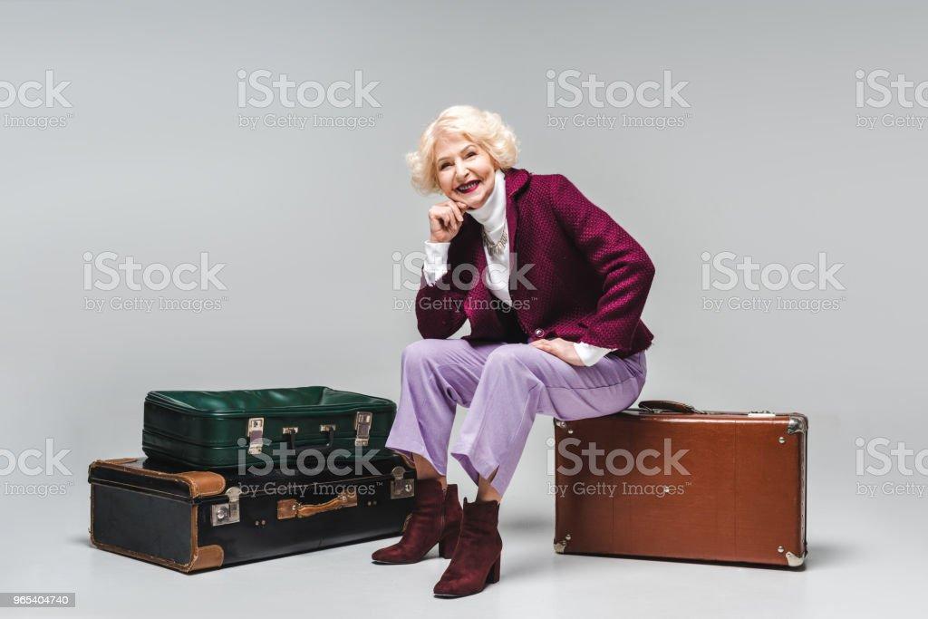 beautiful senior woman sitting on vintage suitcase on grey zbiór zdjęć royalty-free