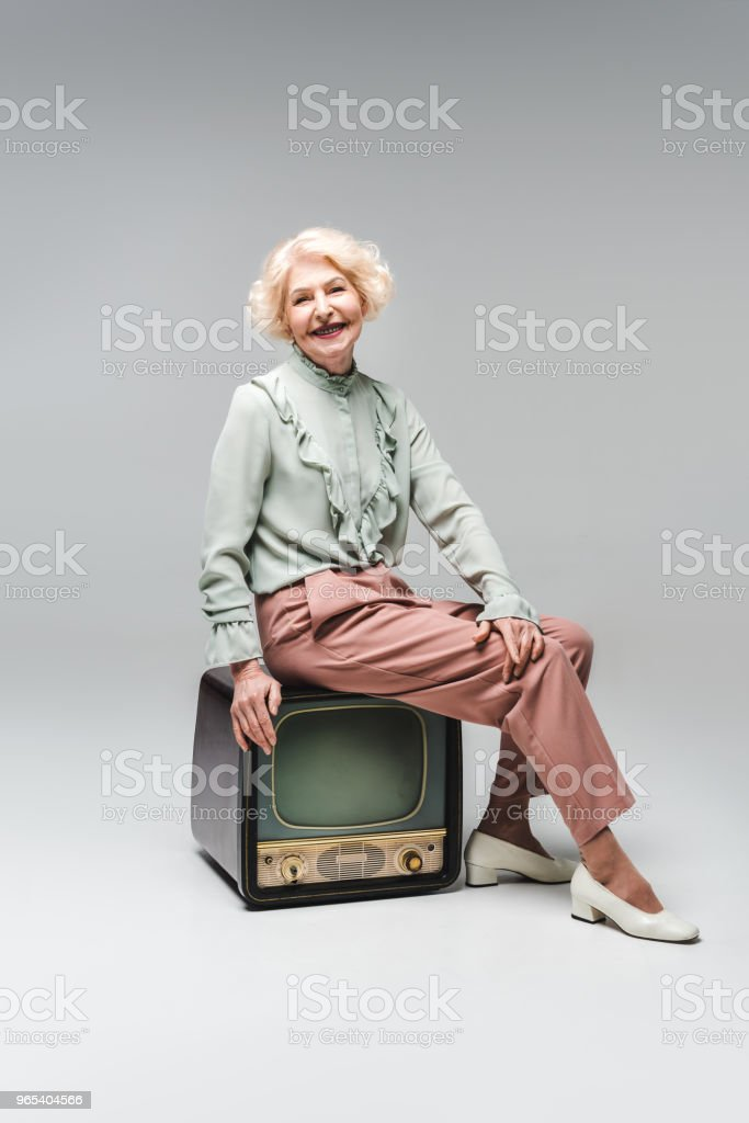 beautiful senior woman sitting on vintage tv on grey zbiór zdjęć royalty-free