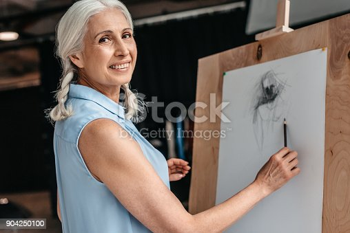 istock beautiful senior woman smiling at camera while drawing with pencil on easel at art class 904250100