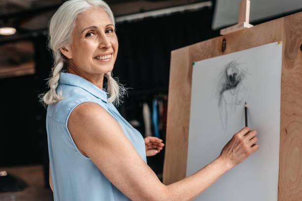 hermosa mujer senior sonriendo a cámara mientras dibujo con lápiz en caballete en clase de arte - clase de arte fotografías e imágenes de stock