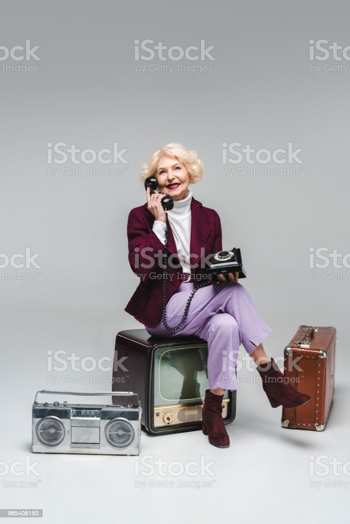 beautiful senior woman talking by phone while sitting on vintage tv on grey zbiór zdjęć royalty-free