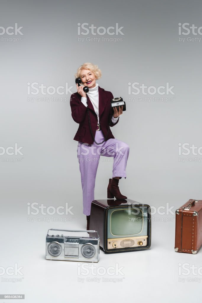 beautiful senior woman talking by phone while standing on vintage tv on grey zbiór zdjęć royalty-free