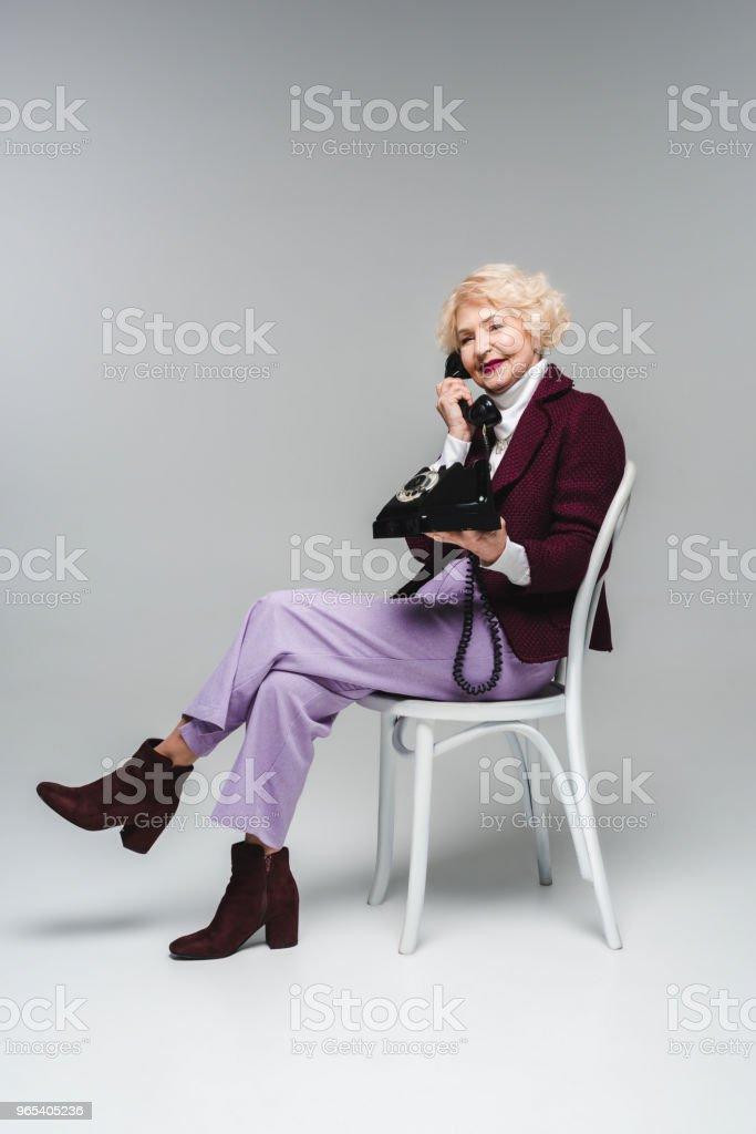 beautiful senior woman talking by vintage phone while sitting on chair on grey zbiór zdjęć royalty-free