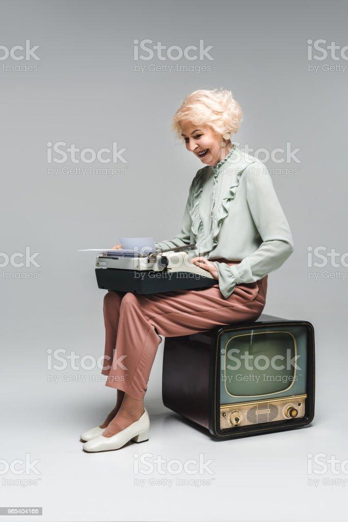 linda mulher sênior usando máquina de escrever enquanto está sentado sobre vintage tv no cinza - Foto de stock de Adulto royalty-free
