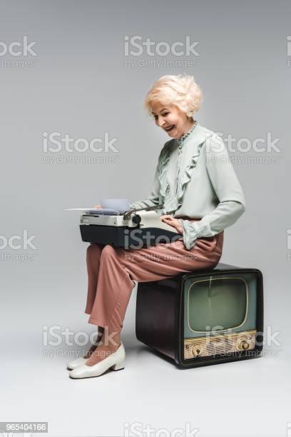 Foto de Linda Mulher Sênior Usando Máquina De Escrever Enquanto Está Sentado Sobre Vintage Tv No Cinza e mais fotos de stock de Adulto