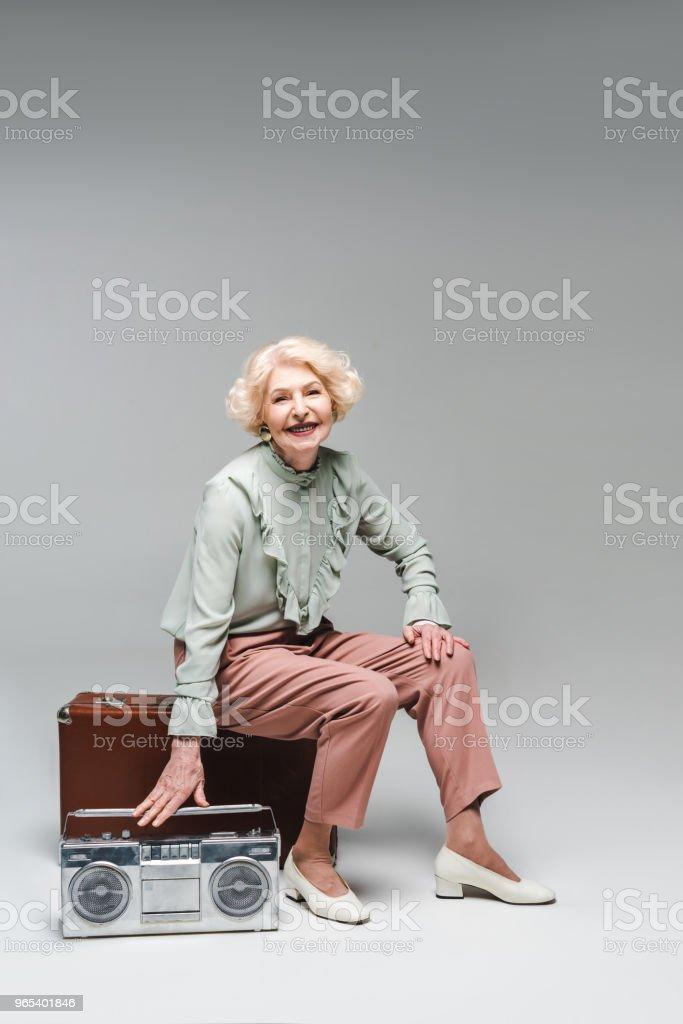 beautiful senior woman with boombox sitting on vintage suitcase on grey zbiór zdjęć royalty-free