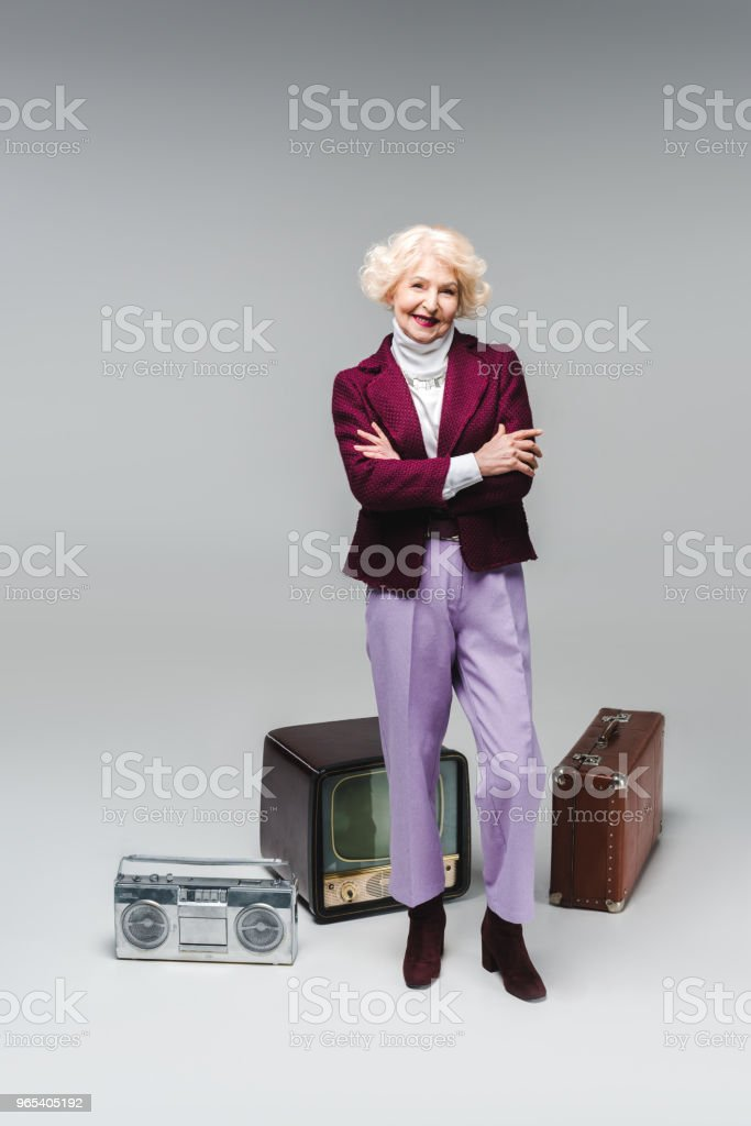 belle femme senior avec bras croisés debout devant vintage tv, boombox et valise sur fond gris - Photo de A la mode libre de droits