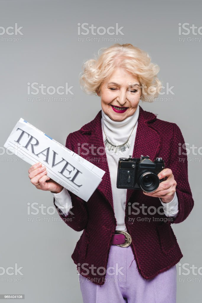 beautiful senior woman with travel newspaper and film camera isolated on grey royalty-free stock photo