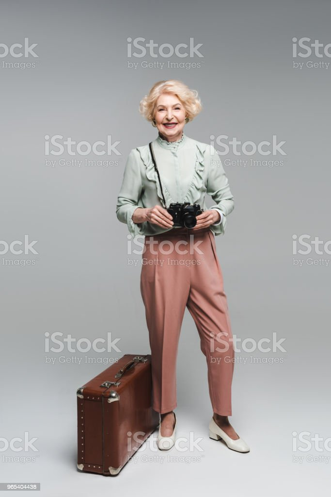beautiful senior woman with vintage suitcase and film camera on grey royalty-free stock photo