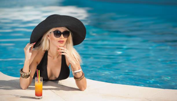Schöne sinnliche Blondine mit entspannenden modische Sonnenbrillen in den Pool mit einem Saft. Attraktive Langhaar Frau in schwarzen tief ausgeschnittenen Badeanzug am Pool. junge Frau, Schnapsglas Sommer Saft. – Foto