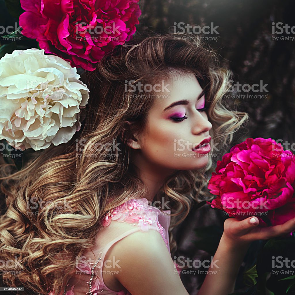 Beautiful sensual blonde woman posing near peony flowers. Girl with long healthy hair and clean skin. Creative colors and Artistic processing. stock photo