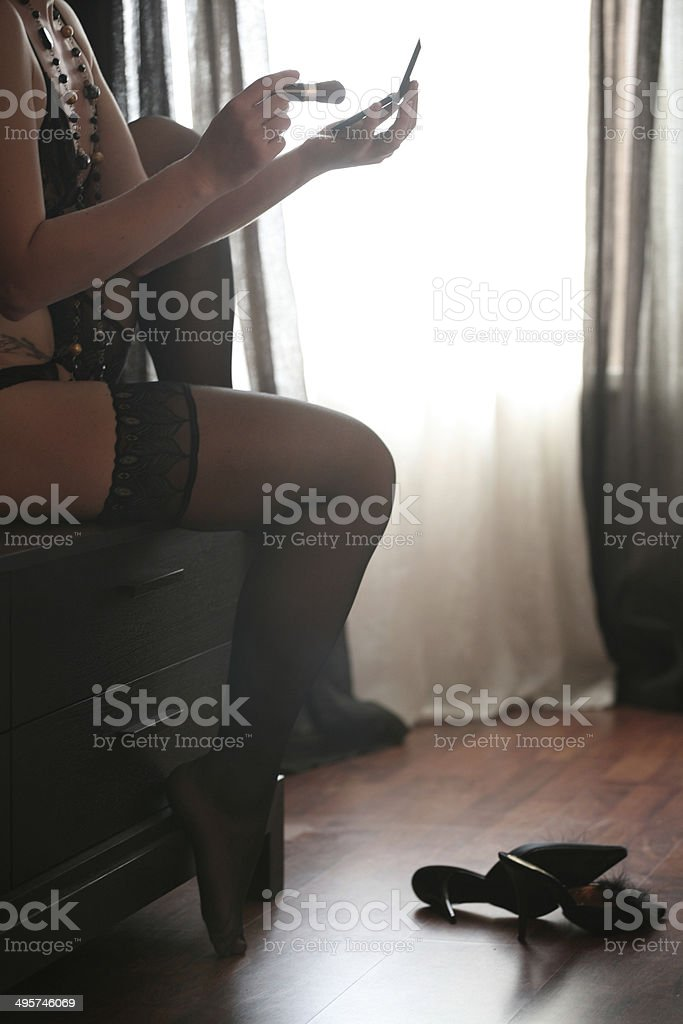 Beautiful, sensual woman in black lace lingerie making make-up stock photo