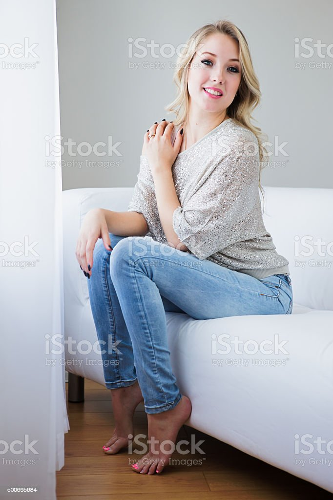 Beautiful sensual young woman sitting on sofa and smiling stock photo