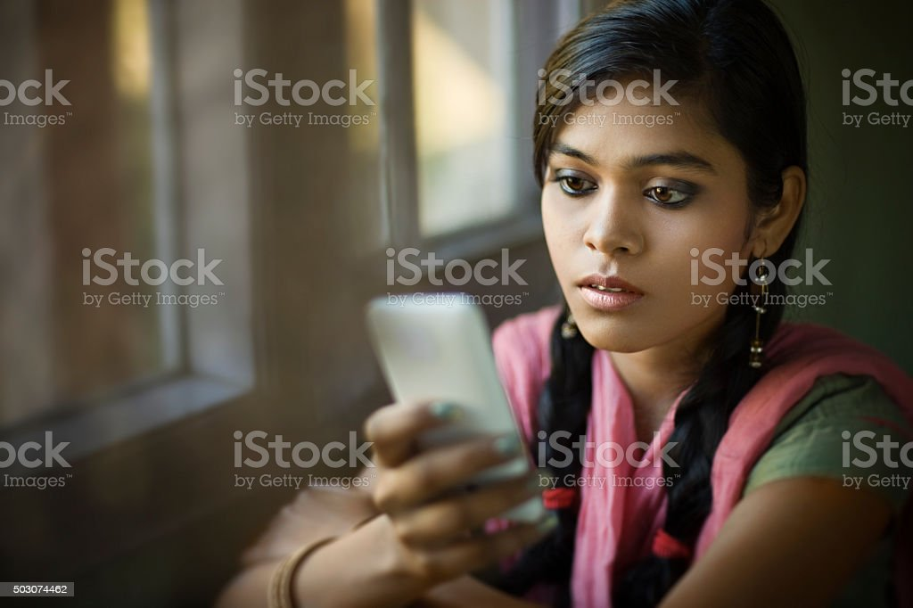 Beautiful serene Indian girl reading SMS sitting near window. stok fotoğrafı