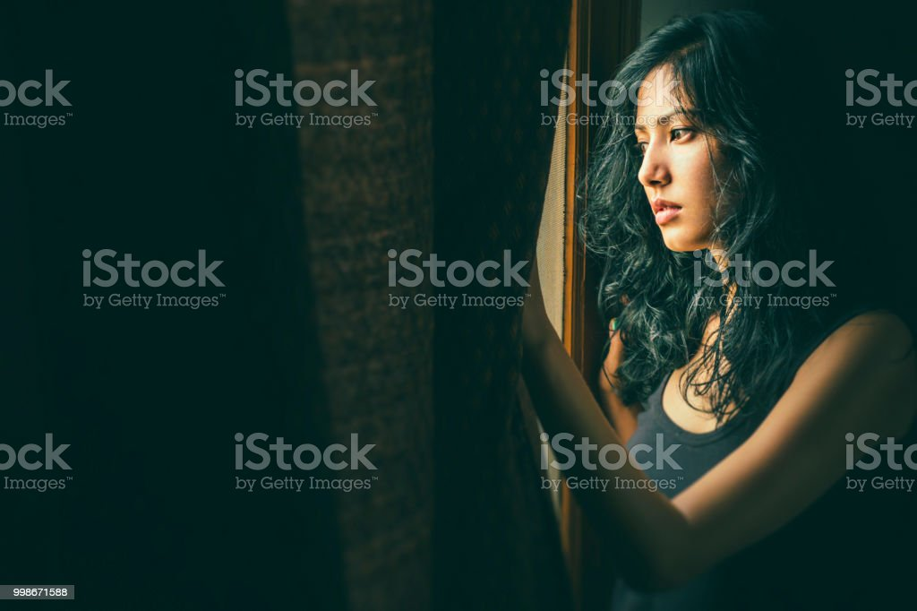 Beautiful serene young woman thinks near window. Portrait of Asian, Indian beautiful serene young woman stands near window at home. She holds the curtain, looks outside the window and thinks deeply with blank expression. Adult Stock Photo