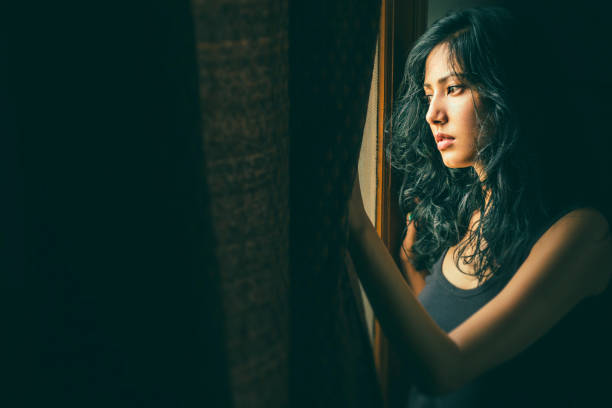 Beautiful serene young woman thinks near window. stock photo