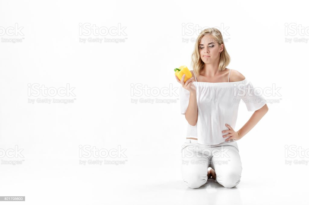 Beautiful Serious Blonde Woman In White Blouse Looks At Yellow Bell Pepper Healthy Eating And Diet Stock Photo Download Image Now