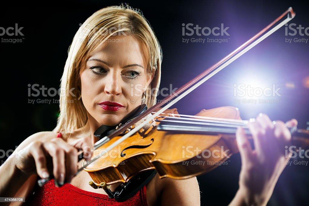 Beautiful serious woman playing violin. stock photo