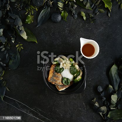Beautiful Serving Branzino or Seabass Fillet with Bisque Sauce and Spinach Top View. Exquisite Delicacy Italian Dish with Grilled Spigola or Sea Bass on Dark Stone and Leaves Background
