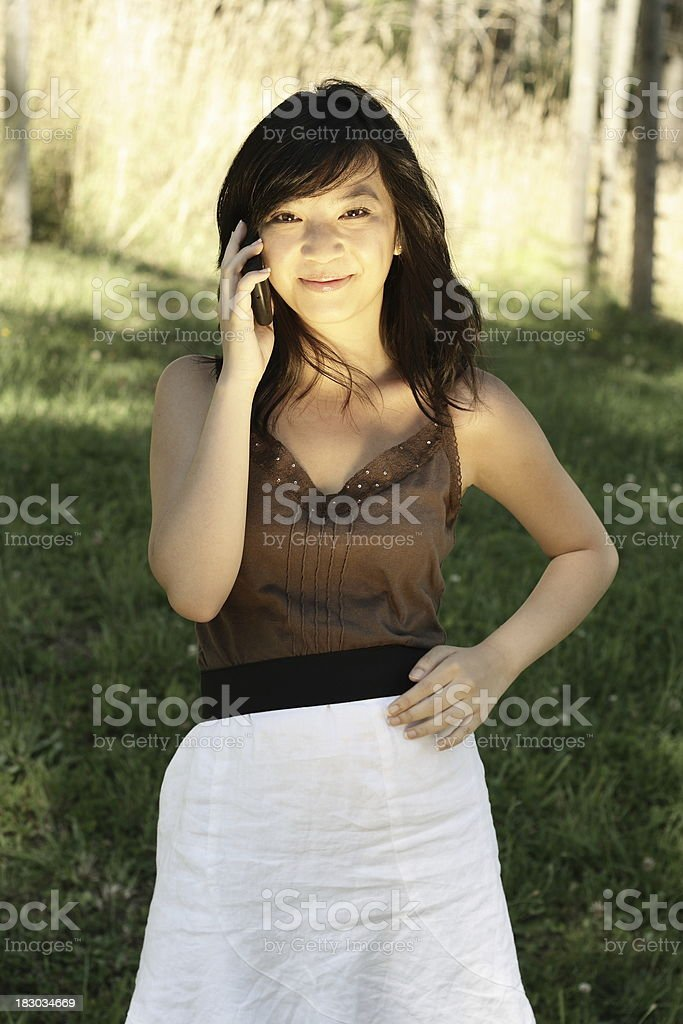 beautiful sexy oriental girl, talking on cell phone happy stock photo