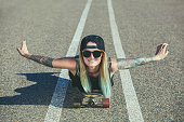 A beautiful, sexy blond hipster with blue hair in a tattoo is riding a longboard on an asphalt road.