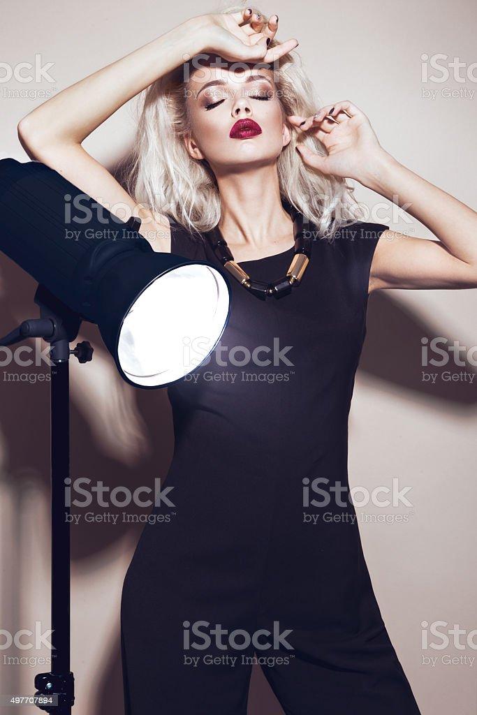 Beautiful sexy blonde girl with sensual lips, fashion hair, black stock photo