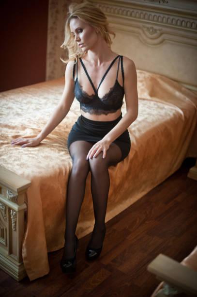 Schöne sexy blonde junge Frau trägt schwarze Dessous im Bett liegen. Modische Sanien mit attraktivem Körper posiert provokativ, Indoor-Shot. Sinnliches Mädchen mit Strumpf und BH auf dem Bett im Hotel – Foto