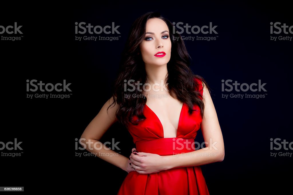 Beautiful sexy brunette with red low cut dress stock photo