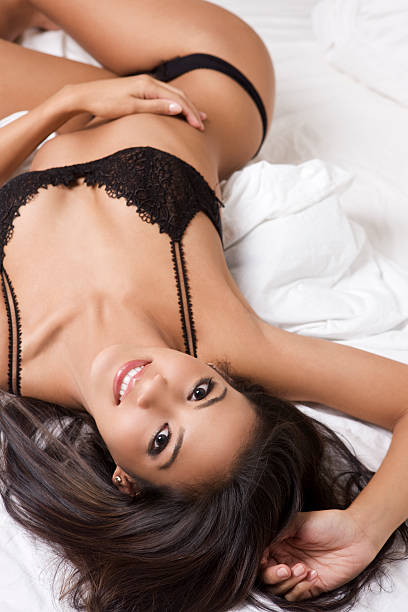 beautiful, sexy brunette woman in black lingerie, lying on bed - hawaiian ethnicity stock photos and pictures