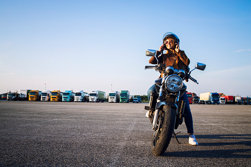 Beautiful sexy brunette woman in leather jacket sitting on retro style motorcycle getting ready for the ride. Riding motorbike. Copy space for text provided.