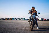 istock Beautiful sexy brunette woman in leather jacket sitting on retro style motorcycle getting ready for the ride. Riding motorbike. Copy space for text provided. 1272788032