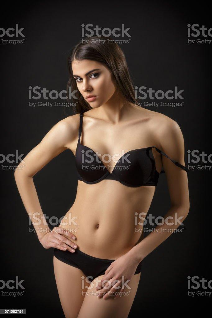 e5682fae4 bela mulher sexy morena posar em lingerie preta sobre fundo preto. Sedutor  e atraente slim