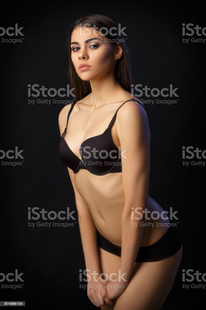 f0c45d8b9 bela mulher sexy morena posar em lingerie preta sobre fundo preto. Sedutor  e atraente slim