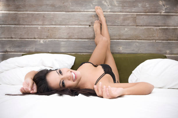 beautiful sexy brunette young woman in lingerie on bed, copyspace - hawaiian ethnicity stock photos and pictures