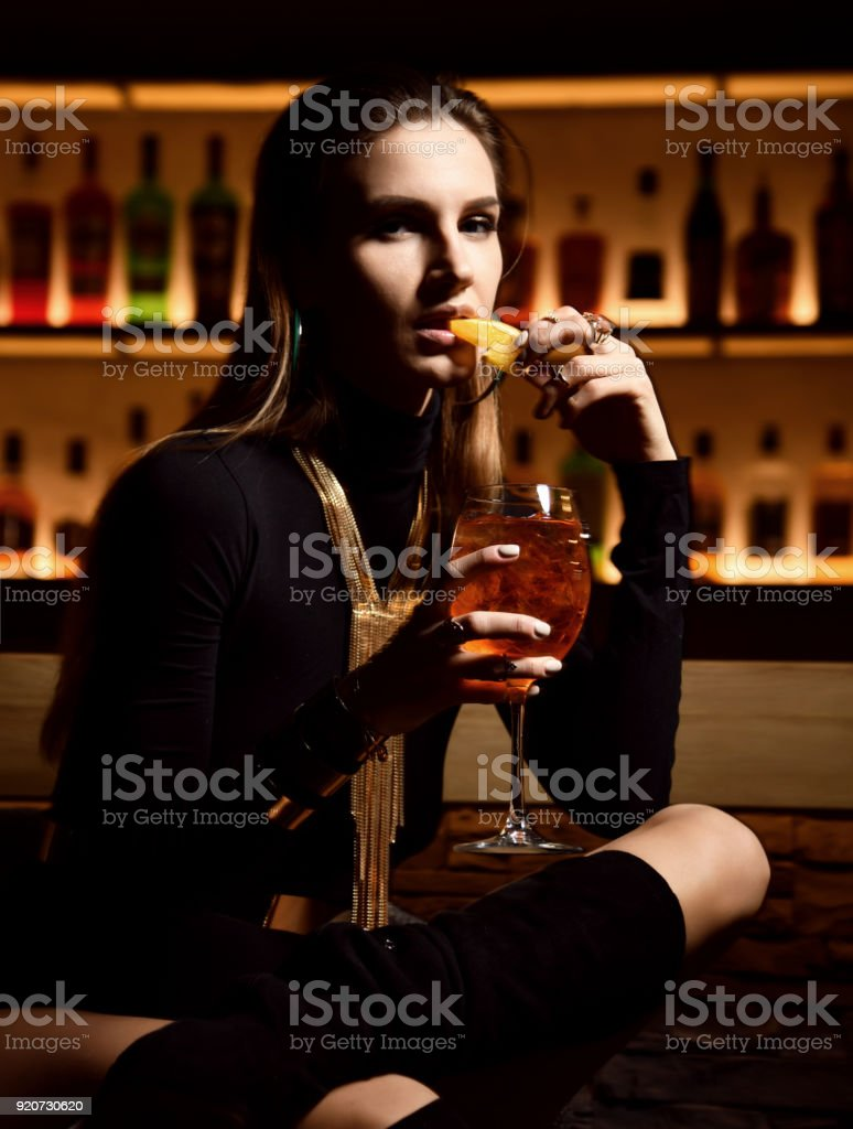 Beautiful sexy fashion brunette woman in bar restaurant relaxing drinking orange aperol sprit cocktail stock photo