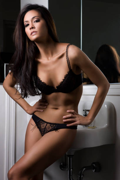 beautiful sexy tan brunette young woman wearing lingerie in bathroom - hawaiian ethnicity stock photos and pictures
