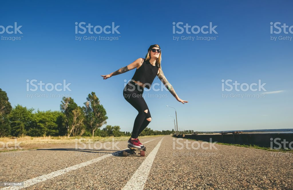 A beautiful, sexy hipster blonde with blue hair in tattoo ride a longboard stock photo