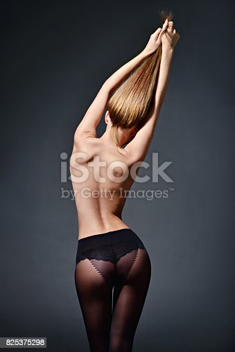 istock Beautiful sexy lady in elegant tights isolated on a black background 825375298