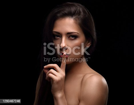 Beautiful sexy long hair girl showing secret sign holding the finger near the lips and looking passion. Closeup portrait isolated on black baclground with empty copy space