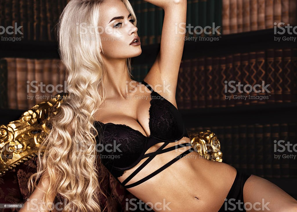 Beautiful sexy long-haired blond woman in black lingerie posing stock photo