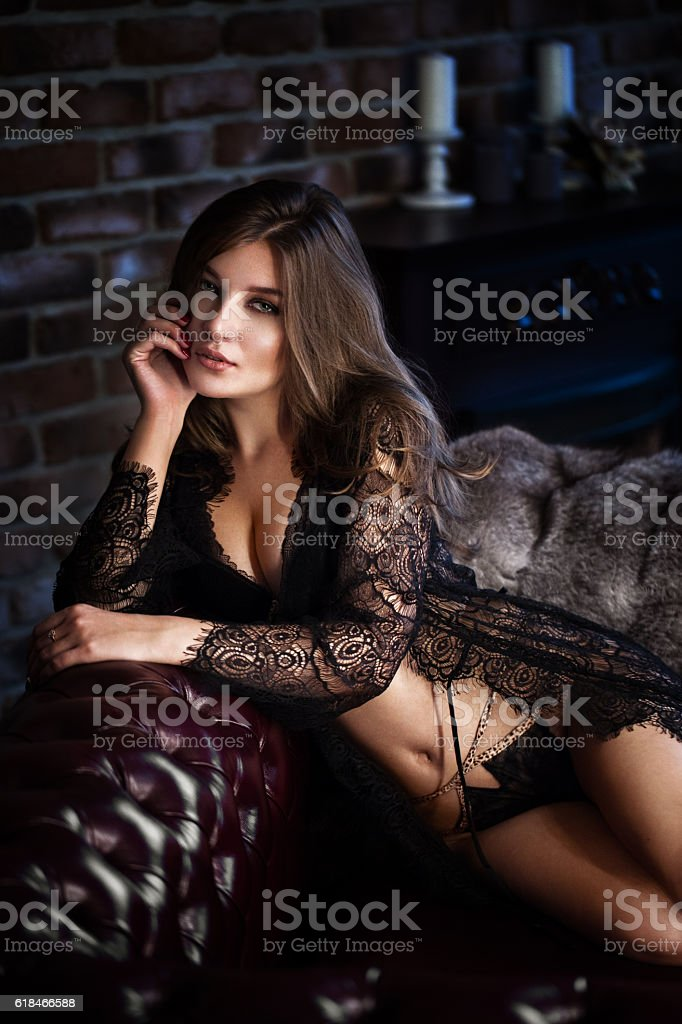Beautiful sexy long-haired woman in black lingerie posing in stock photo