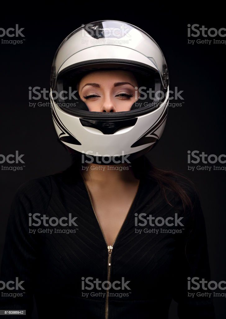 Beautiful sexy makeup woman looking in white motorcycle helmet on black background. Closeup dark portrait royalty-free stock photo
